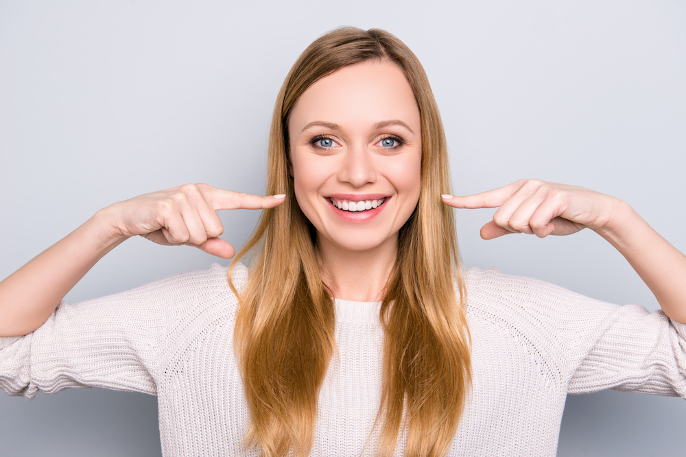Portrait of joyful satisfied girl gesturing her beaming white healthy teeth with two forefingers looking at camera isolated on grey background. Orthodontic concept